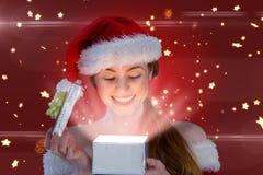 Samengesteld beeld van sexy meisje in santakostuum die een gift openen Stock Fotografie