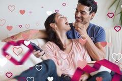 Samengesteld beeld van speels paar die op TV letten terwijl het eten van popcorn Stock Afbeeldingen