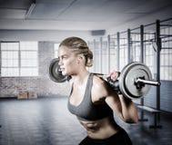 Samengesteld beeld van spiervrouw die zware barbell opheffen Royalty-vrije Stock Foto's