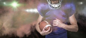 Samengesteld beeld van sportenspeler die helm dragen terwijl het houden van bal Stock Foto