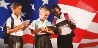 Samengesteld beeld van studenten in uniformen die digitale tabletten gebruiken royalty-vrije stock fotografie