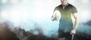 Samengesteld beeld van taaie de holdingsbal van de rugbyspeler Royalty-vrije Stock Foto's