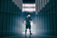 Samengesteld beeld van terug gedraaide rugbyspeler die een bal 3d houden Stock Foto