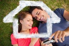 Samengesteld beeld van twee glimlachende vrienden die foto's op een camera bekijken Stock Fotografie