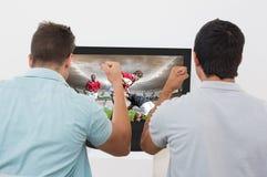 Samengesteld beeld van twee opgewekte voetbalventilators die op TV letten stock illustratie