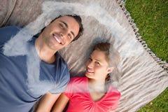 Samengesteld beeld van twee vrienden die naar de hemel kijken terwijl het liggen op een dekbed Stock Foto's
