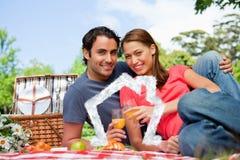 Samengesteld beeld van twee vrienden die terwijl zij glazen tijdens een picknick houden vooruitzien Royalty-vrije Stock Foto