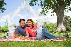 Samengesteld beeld van twee vrienden die terwijl zij glazen vooruitzien houden aangezien zij een picknick hebben Stock Afbeelding