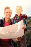 Samengesteld beeld van vader en zijn zoon die een kaart bekijken stock fotografie