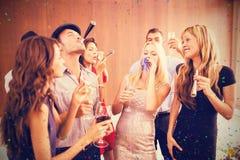 Samengesteld beeld van vrienden die pret hebben terwijl status met dranken royalty-vrije stock foto