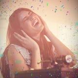 Samengesteld beeld van vrij vrouwelijk DJ die pret hebben terwijl het luisteren muziek op hoofdtelefoon Royalty-vrije Stock Fotografie