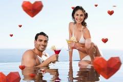 Samengesteld beeld van vrolijk paar die cocktails in de pool hebben Stock Foto's
