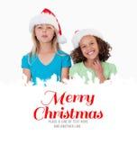 Samengesteld beeld van vrolijke meisjes met Kerstmishoeden Stock Foto's