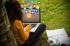 Samengesteld beeld van vrouw die laptop in 3d park met behulp van Royalty-vrije Stock Afbeeldingen