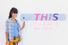 Samengesteld beeld van vrouw het schilderen muurblauw en het glimlachen Royalty-vrije Stock Foto