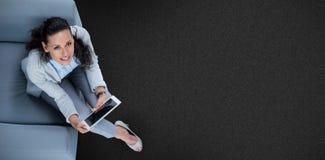Samengesteld beeld van vrouw op haar tablet die omhoog eruit zien stock foto's