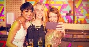 Samengesteld beeld van vrouwelijke vrienden die selfie uit mobiele telefoon nemen terwijl het hebben van champagne stock afbeeldingen
