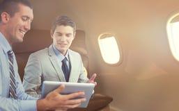 Samengesteld beeld van zakenlieden die samen met laptop en tablet werken Stock Afbeelding