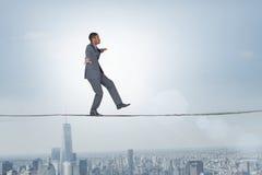 Samengesteld beeld van zakenman die een in evenwicht brengende handeling uitvoeren royalty-vrije stock afbeelding