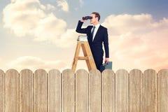 Samengesteld beeld van zakenman het kijken op een ladder stock foto