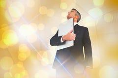 Samengesteld beeld van zakenman in kostuum die zijn laptop trots houden Royalty-vrije Stock Foto's