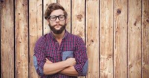 Samengesteld beeld van zekere hipster die oogglazen met gekruiste wapens dragen Stock Foto