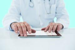 Samengesteld 3d beeld van arts die digitale tablet gebruiken tegen witte achtergrond Stock Afbeelding