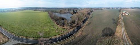 Samengesteld panorama van luchtfoto's en luchtfoto's van een rechte weg naast een vijver en een gebied, abstract effect toe te sc Stock Fotografie