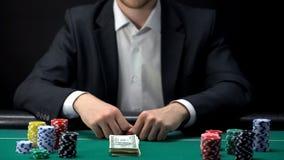 Samengestelde casinocliënt die al spaanders en de stapel van geld, zekere gokker wedden stock foto's