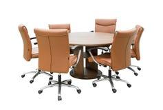 Samenkomende houten lijst en bruine stoelen in vergaderzaal geïsoleerd o stock afbeeldingen