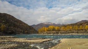 Samenloop van twee rivieren in bergen De herfst, gouden uurlicht Beweging van rivieren en wolken stock videobeelden