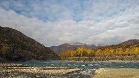 Samenloop van twee rivieren in bergen De herfst, gouden uurlicht Beweging van rivieren en wolken stock video