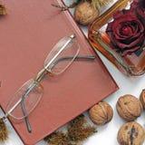 samenstelling Cognac, een gesloten boek, glazen en kastanjes stock foto