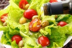 Samenstelling gegoten olijfolie, olijven, paddestoelen, citroen, knoflook, ui, sla stock afbeelding
