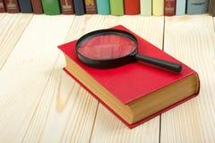 Samenstelling met boek met harde kaftboeken en vergrootglas op de lijst Terug naar school, exemplaarruimte schaar en potloden op  Stock Foto