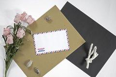 Samenstelling met brief en roze bloemen op witte achtergrond Overzeese vakantie of reisherinnering op lijst Royalty-vrije Stock Afbeeldingen