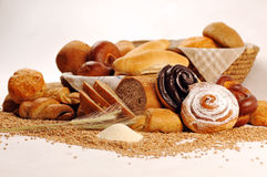 Samenstelling met brood en broodjes in rieten mand, combinatie zoete gebakjes voor bakkerij of markt met tarwe Stock Fotografie