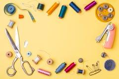Samenstelling met draden en naaiende toebehoren - schaar, centimeter, spelden op gele achtergrond stock afbeelding
