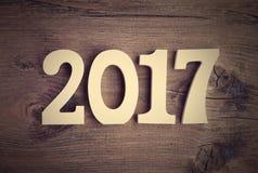 Samenstelling met een houten aantal 2017 als symbool van het komende Nieuwjaar Gelukkig Nieuwjaarconcept op een rustieke houten a Stock Afbeelding