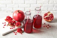 Samenstelling met flessen vers granaatappelsap stock fotografie