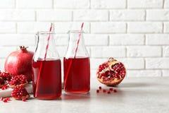 Samenstelling met flessen vers granaatappelsap op lijst stock afbeeldingen
