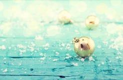 Samenstelling met gouden Kerstmisballen op rustiek turkoois hout Stock Afbeelding