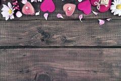 Samenstelling met kaarsen, bloemen en harten op donker rustiek hout Stock Afbeelding