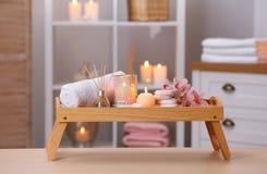 Samenstelling met kaarsen, bloemen en stenen op houten lijst royalty-vrije stock afbeeldingen