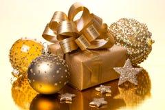 Samenstelling met Kerstmisballen en giftvakje op gouden lijst Stock Fotografie