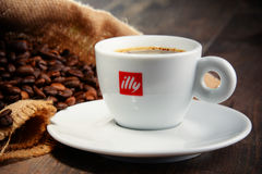 Samenstelling met kop de koffie en bonen van Illy Stock Fotografie