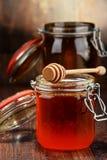 Samenstelling met kruiken honing op houten lijst Stock Foto