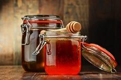 Samenstelling met kruiken honing op houten lijst Stock Afbeeldingen