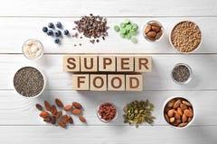 Samenstelling met kubussen en assortiment van superfoodproducten in kommen Royalty-vrije Stock Foto's