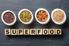 Samenstelling met kubussen en assortiment van superfoodproducten in kommen op houten achtergrond, Stock Foto